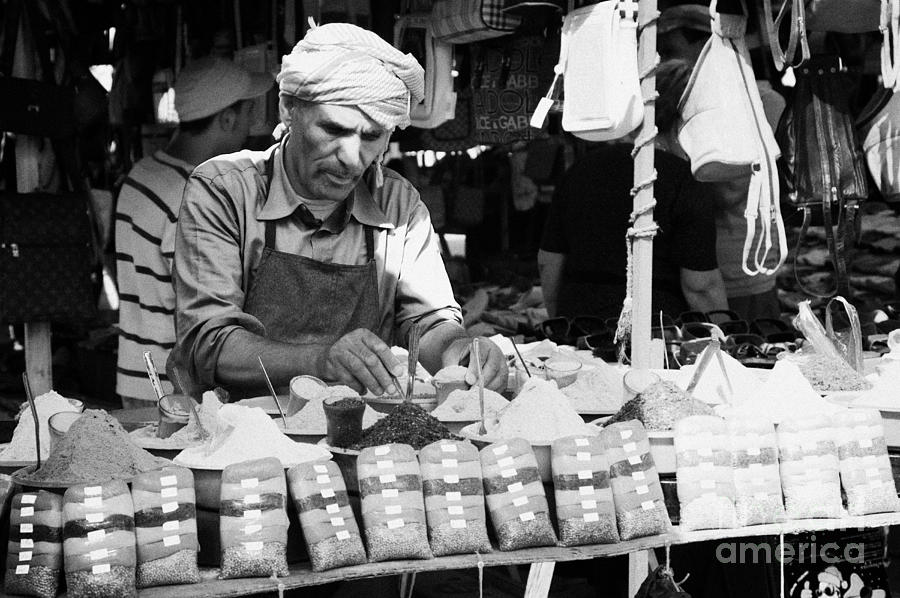 Tunisia Photograph - Local Arab Man Measuring Out A Quantity Of Spice For Sale On Stall Of Spices At The Market In Nabeul Tunisia by Joe Fox
