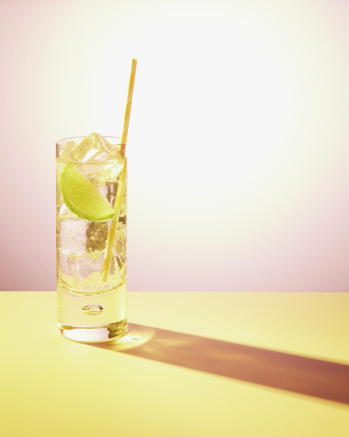 Long Drink In Glass With Lime And Straw Photograph by Felicity Mccabe