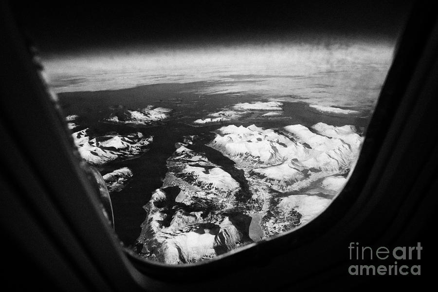 Looking Photograph - Looking Out Of Aircraft Window Over Snow Covered Fjords And Coastline Of Norway  by Joe Fox