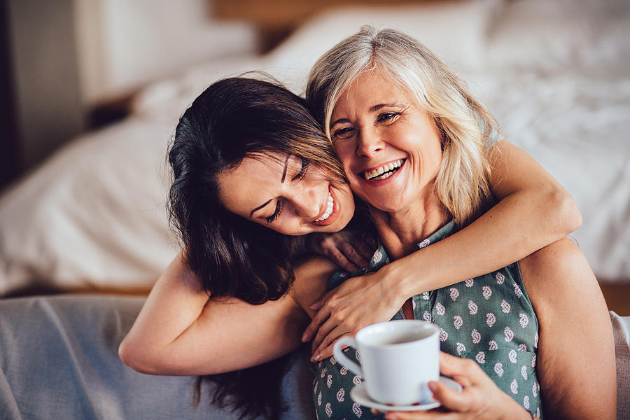 Loving adult daughter embracing cheerful senior mother at home Photograph by Wundervisuals