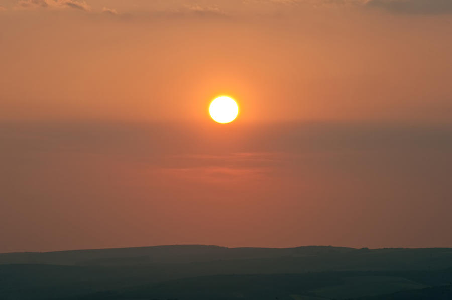 Sun Photograph - Low Setting Sun Over Distant Landscape by Matthew Gibson