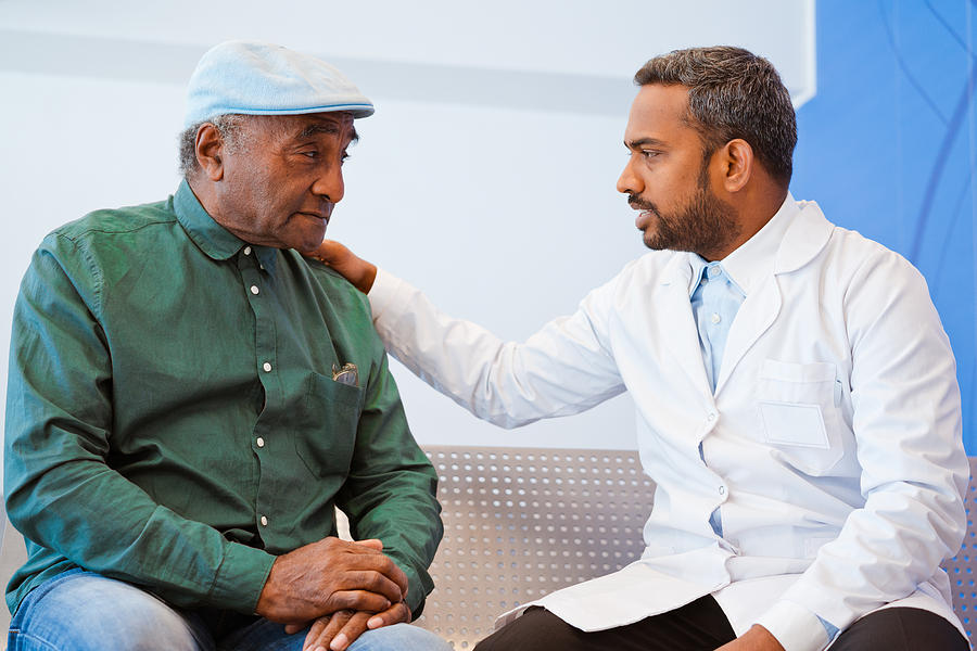 Male doctor consoling senior patient at hospital Photograph by Izusek