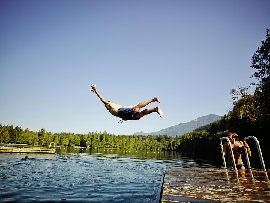 Man Diving Off Dock Into Mountain Lake Photograph by Thomas Barwick