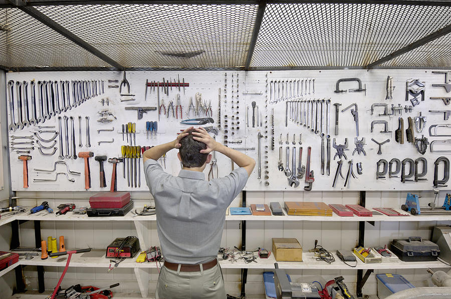 Man Holding Head By Wall Of Tools Photograph by Lester Lefkowitz