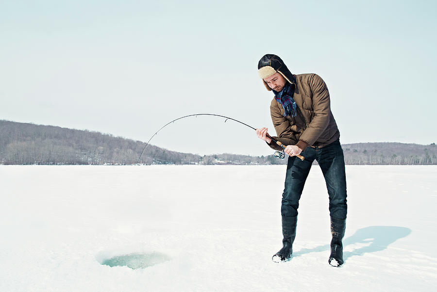 Man Ice Fishing On Frozen Lake Photograph by Andy Ryan