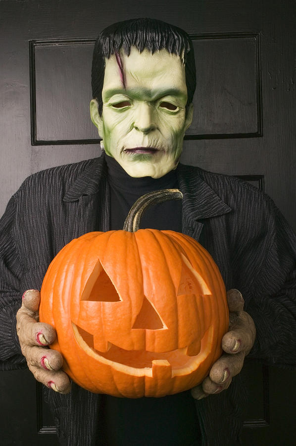 Man In Frankenstein Costume Holding Jack Olantern Photograph by Garry Gay