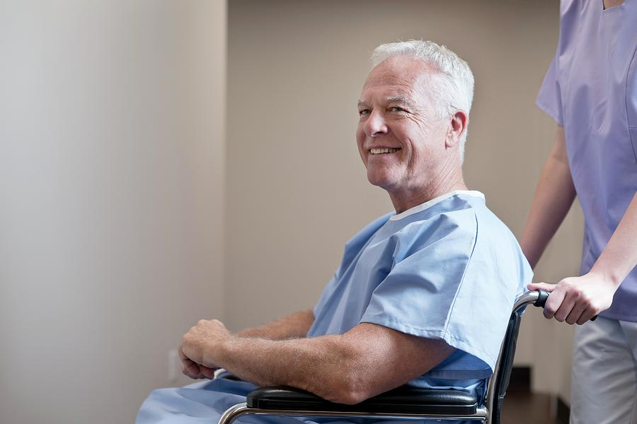 Adult Photograph - Man In Hospital Gown In Wheelchair by Science Photo Library