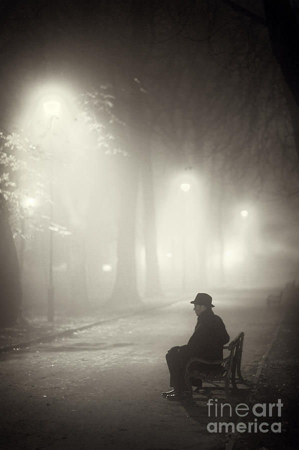Man In Overcoat And Hat Sitting On A Park Bench At Night In Fog