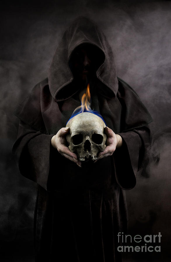 man in the hooded cloak holding burning human skull in his