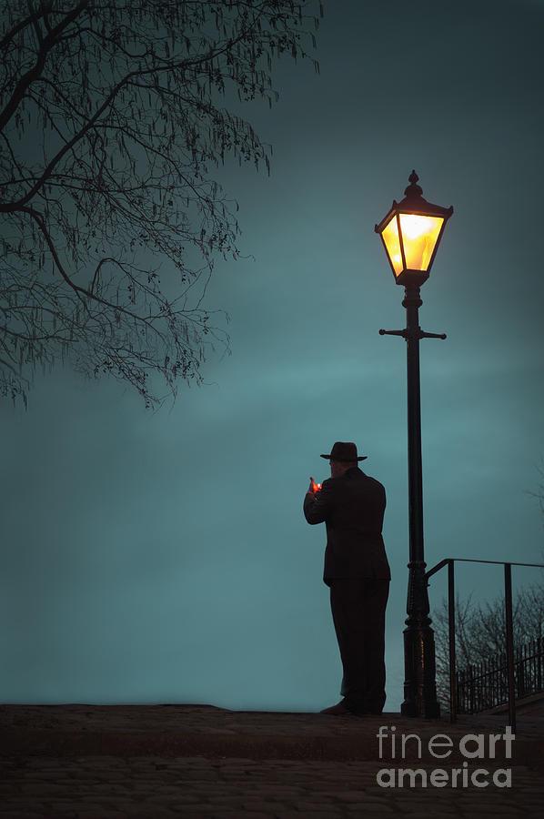 Man Lighting A Cigarette Beneath An Illuminated Street