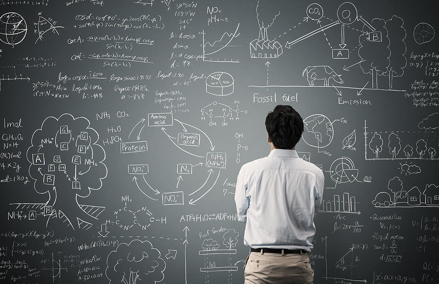 Man looking to formula and picture on blackboard Photograph by Yagi Studio