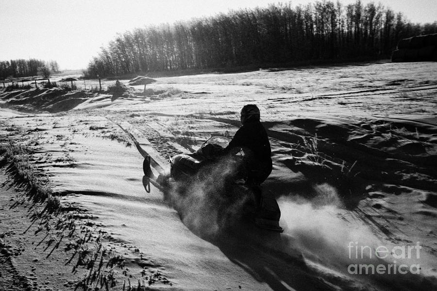 Man Photograph - man on snowmobile crossing frozen fields in rural Forget canada by Joe Fox