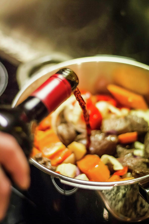 Man Pouring Wine Into Vegetables Photograph by Manuel Sulzer