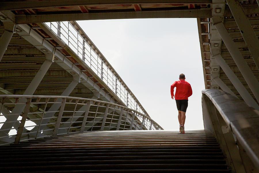 Man Running Up A Bridge Photograph by Chris Tobin