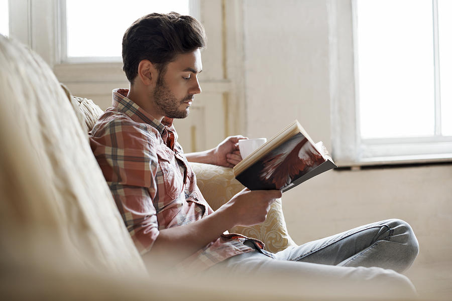 Man sitting on sofa reading book Photograph by Morsa Images