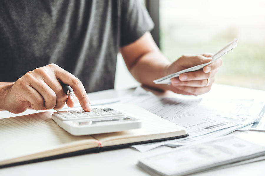 Man using calculator Accounting Calculating Cost Economic bills with money stack step growing growth saving money in home , finance concept Photograph by Sarinyapinngam