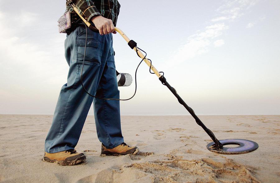 Man using metal detector at beach Photograph by Hill Street Studios