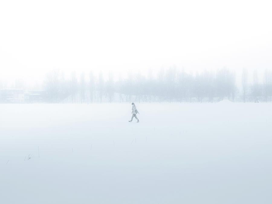 Man Walking Through A Snowfield Photograph by Taketan