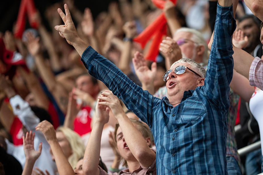 Man with arms raised in a stadium crowd Photograph by Vm