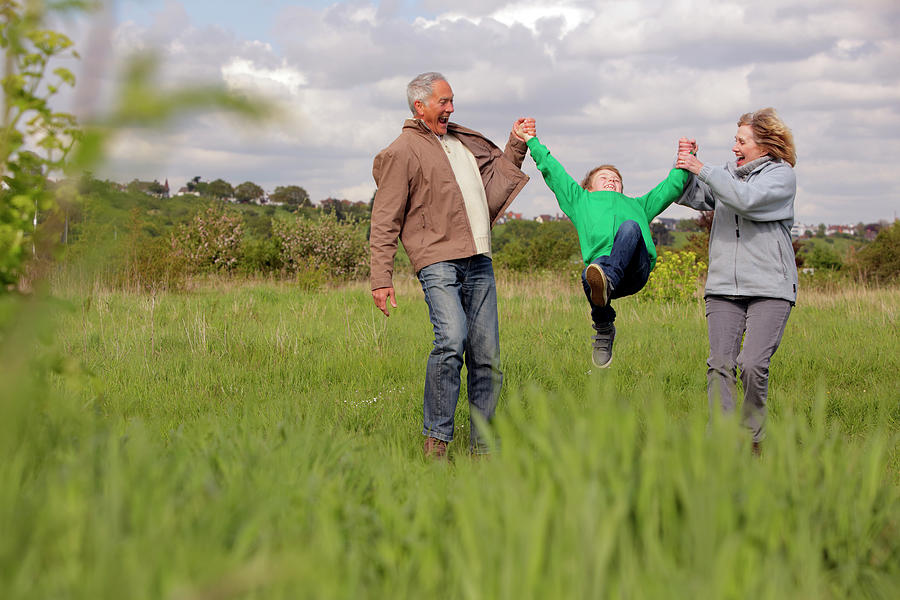 Mature Couple Swinging Grandchild In Photograph by Bloom Productions