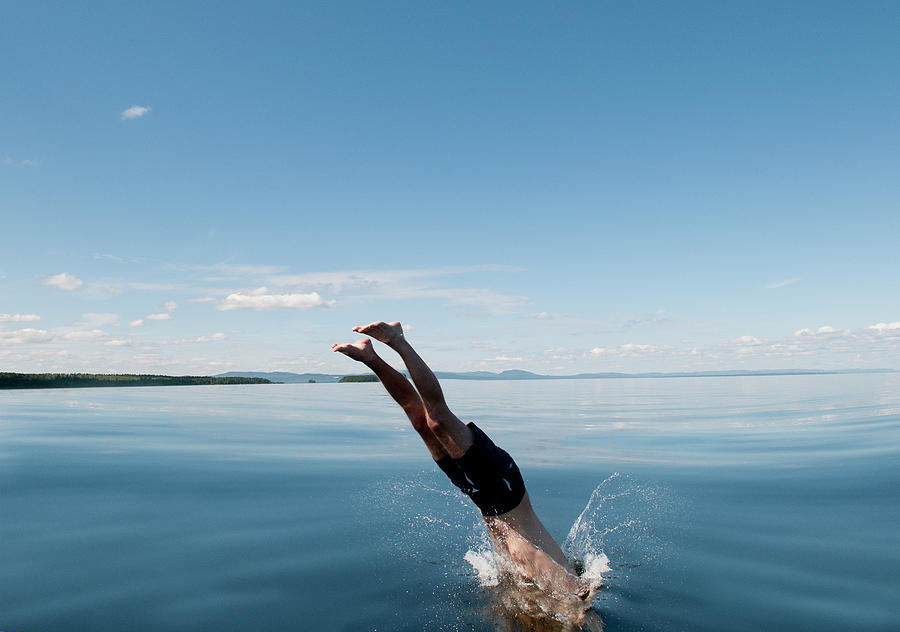 Mature Man Jumping In Sea Photograph by Johner Images