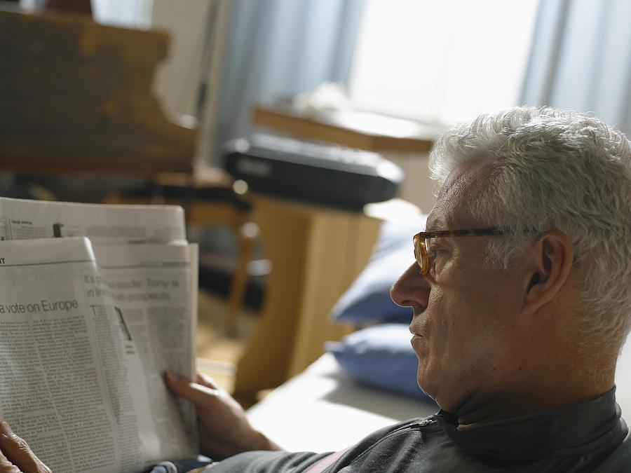 Mature man reading newspaper, close up Photograph by John Howard