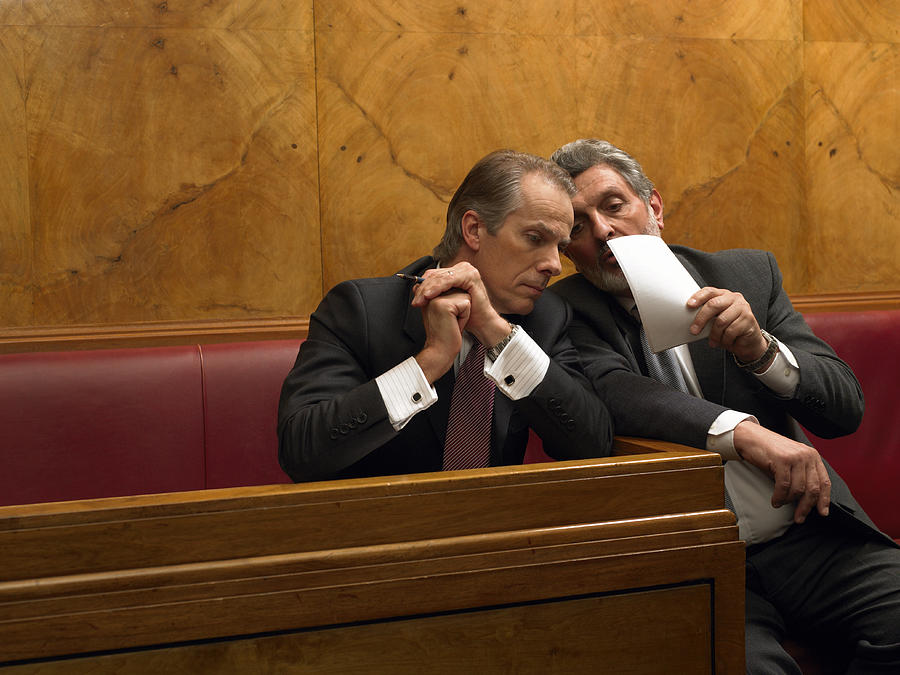 Mature Man Whispering To Colleague In Pew Photograph by Michael Blann