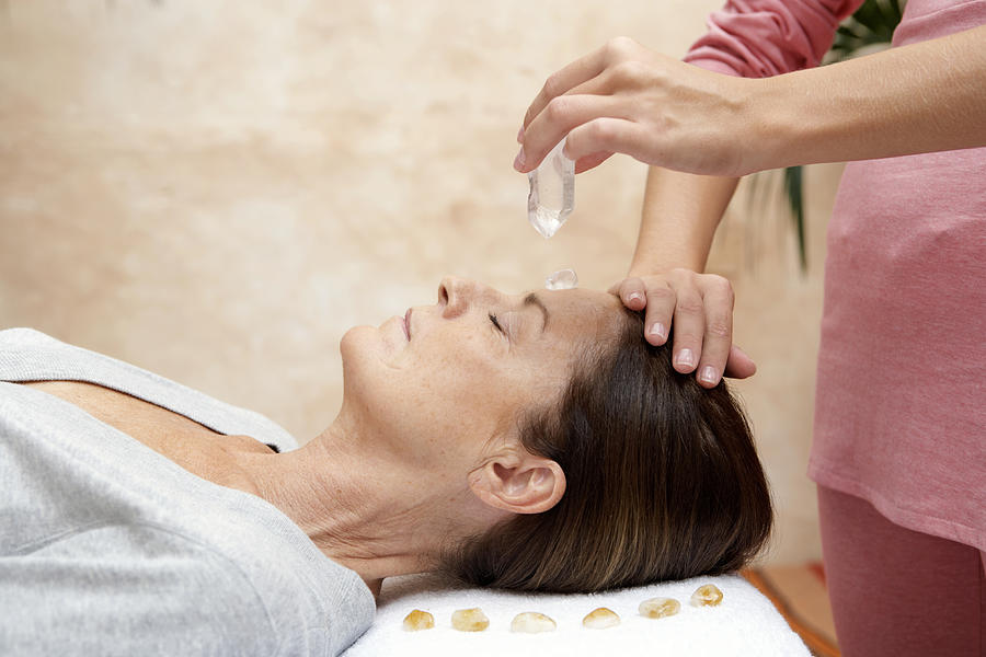 Mature woman receiving crystal healing treatment, eyes closed Photograph by Maria Teijeiro