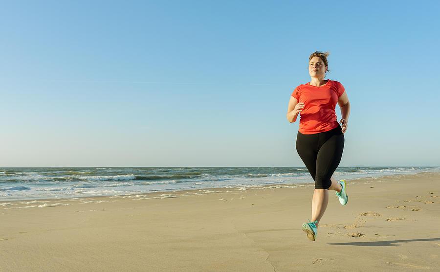 Mature woman running on a beach at sunset Photograph by Mischa Keijser