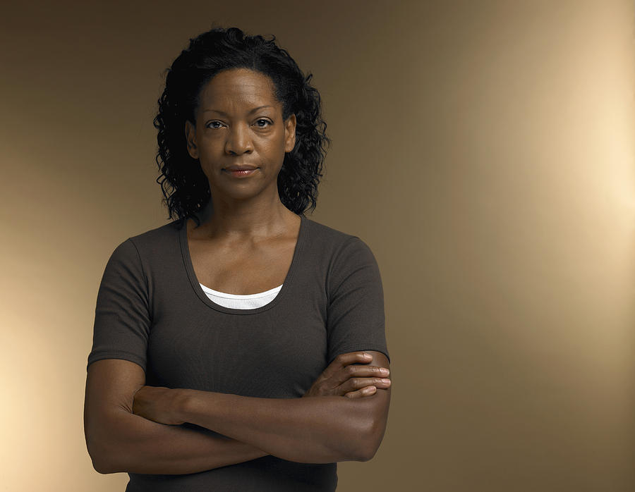 Mature woman standing with arms crossed, portrait Photograph by Christopher Robbins