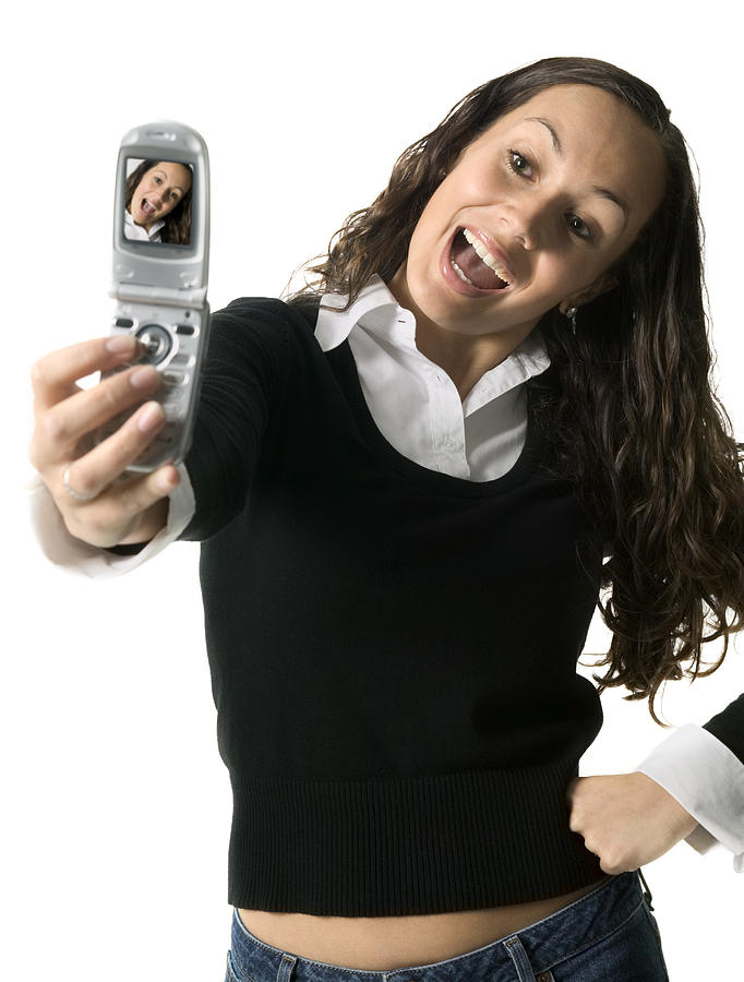 Medium Shot Of A Young Adult Female As She Playfully Poses For Her Camera Phone Photograph by Photodisc