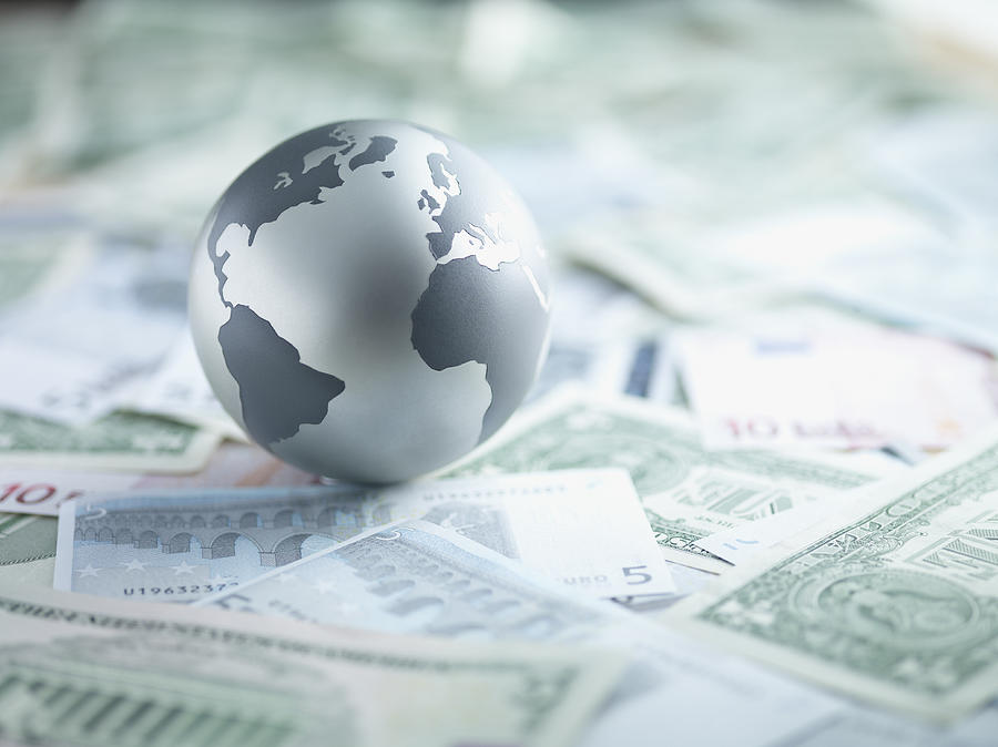 Metal globe resting on paper currency Photograph by Martin Barraud
