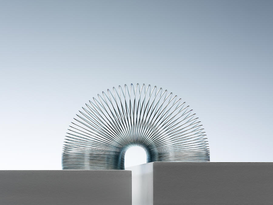 Metal Slinky Spanning Space Between Blocks Photograph by Andy Roberts