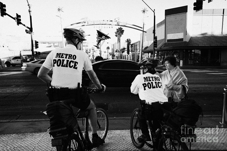 Metro Photograph - metro police bicycle cops help a tourist with directions in downtown Las Vegas Nevada USA by Joe Fox