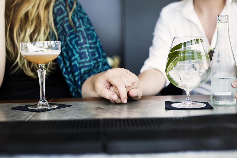Midsection of lesbian couple holding hands with glasses of cocktail on bar counter Photograph by Astrakan Images
