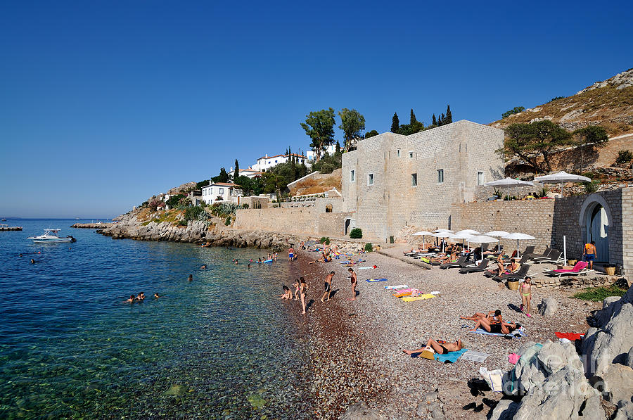 Hydra; Idra; Kaminia; Kamini; Mikro Kamini; Greece; Hellas; Greek; Hellenic; Argosaronic; Saronic; Gulf; Islands; Beach; People; Tourists; Swim; Swimming; Sunbathing; Suntanning; Suntan; Tanning; Castello; Cafe; Cafeteria; Island; Bar; Restaurant; Inn; Holidays; Vacation; Travel; Trip; Voyage; Journey; Tourism; Touristic; Summer; Sunny; Sea; Blue; Sky Photograph - Mikro Kamini Beach by George Atsametakis
