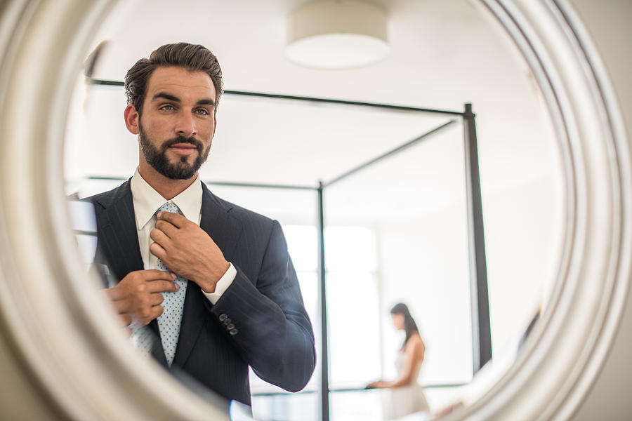 Mirror reflection of young businessman adjusting shirt and tie in hotel room, Dubai, United Arab Emirates Photograph by Antonio Saba