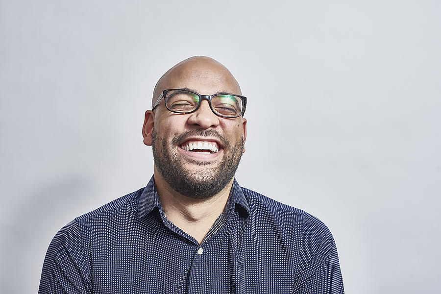 Mixed race male laughing with his head back Photograph by Jamie Garbutt