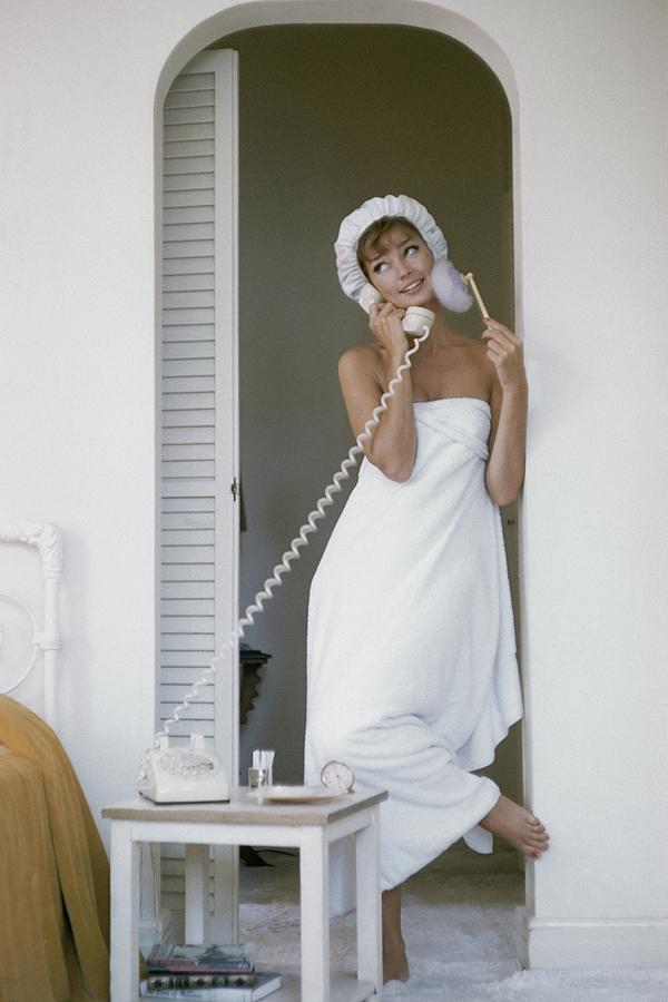 Model Standing In A Bath Towel While Preparing Photograph by Karen Radkai
