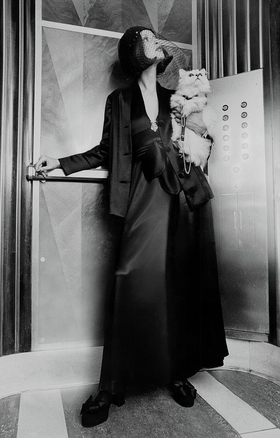 Model Wearing A Larry Aldrich Pantsuit Holding Photograph by Kourken Pakchanian