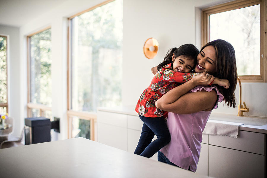 Mother and daughter embracing in kitchen Photograph by MoMo Productions