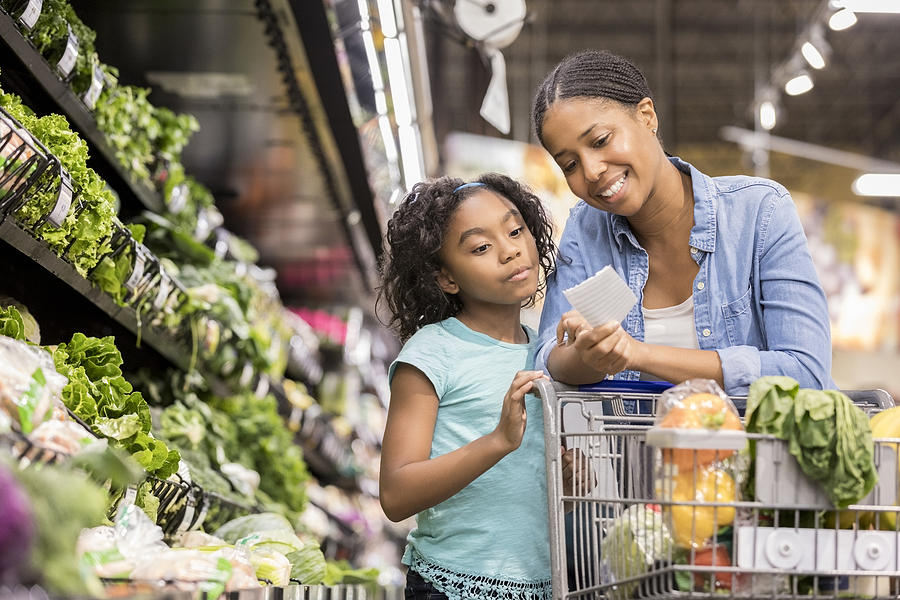 Mother and daughter grocery shop together using list Photograph by SDI Productions