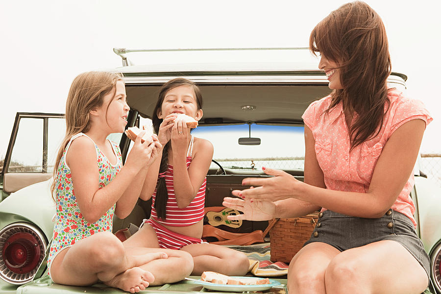Mother And Daughters Eating Sandwiches On Car Boot Photograph by Image Source