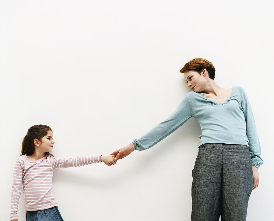 Mother And Her Daughter Stand By A Wall, Reaching Out And Holding Hands Photograph by Dylan Ellis
