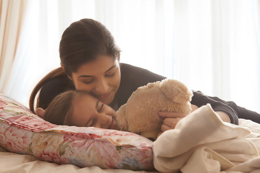 Mother Comforting Daughter In Bed Photograph by India Picture