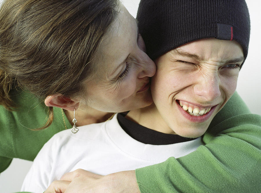 Mother kissing teenage boy (14-16) on cheek, close-up Photograph by Gone Wild
