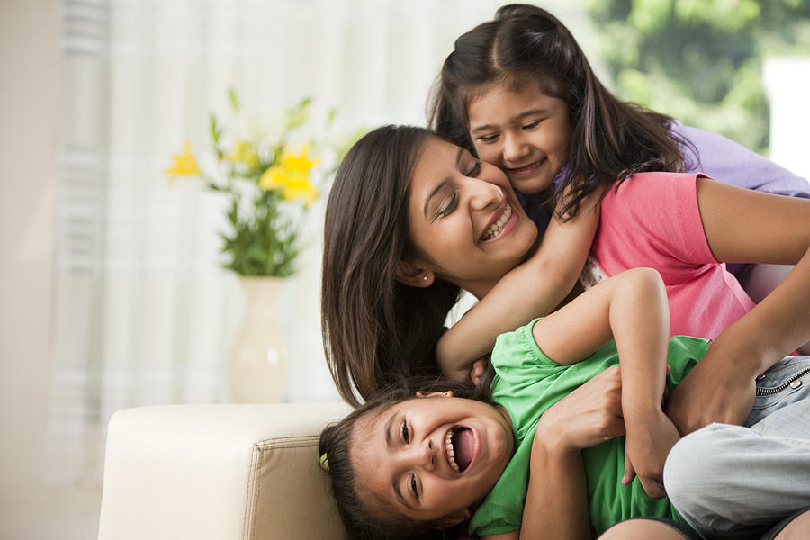 Mother With Daughters (6-7) Sitting On Sofa Photograph by ImagesBazaar