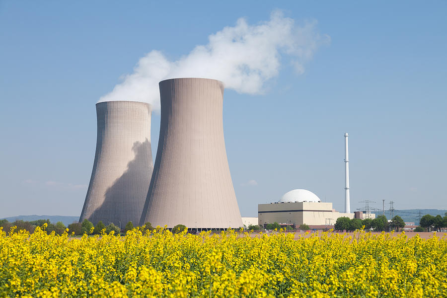 Nuclear power station with steaming cooling towers and canola field Photograph by RelaxFoto.de