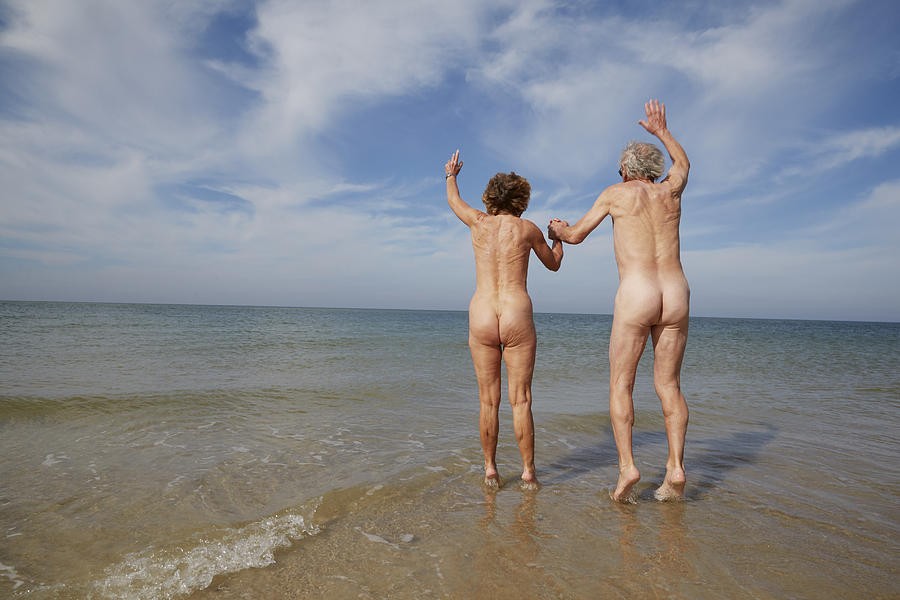 Nude Older Couple Jumping In Water Photograph by Chris Tobin