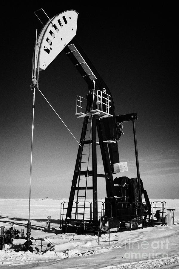 Oil Photograph - oil pumpjack in winter snow Forget Saskatchewan Canada by Joe Fox